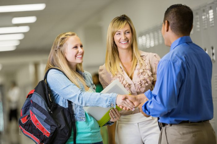 Teacher Welcoming New Student And Mom In Hallway Of School