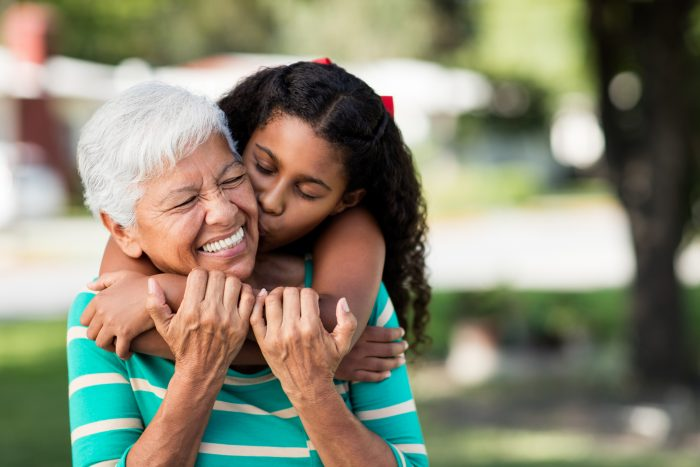 Loving Teen Girl Embracing And Kissing Grandmother