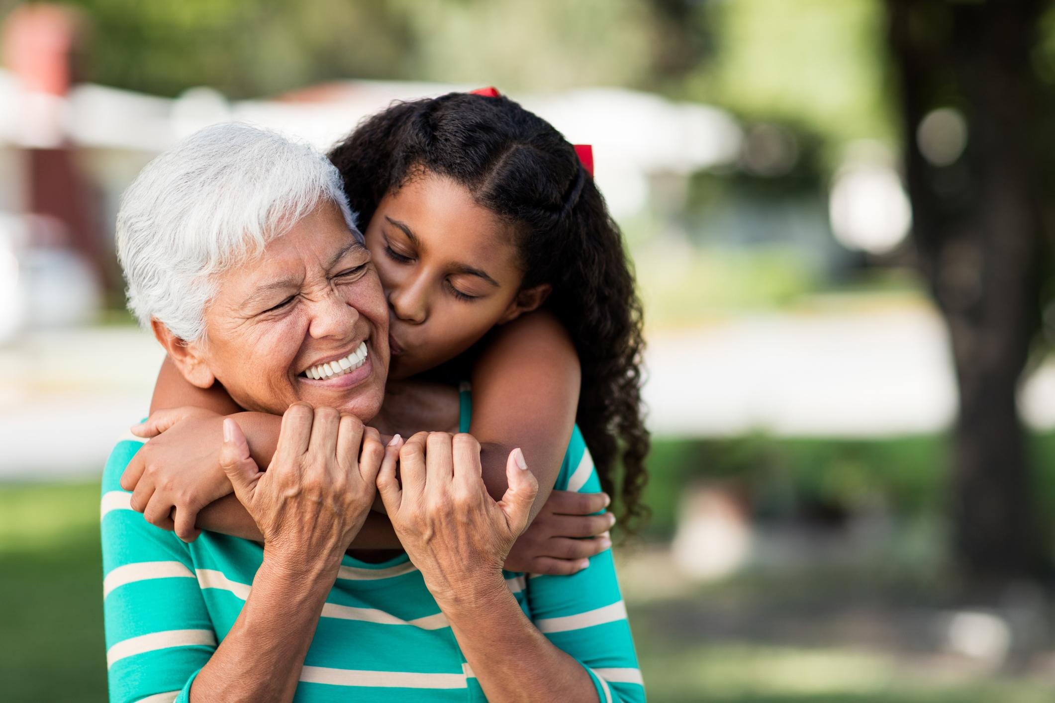Loving Teen Girl Embracing And Kissing Grandmother