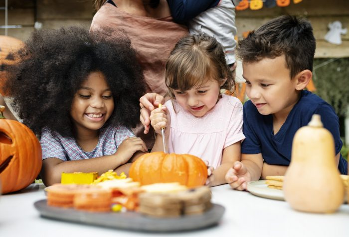 Young Kids Carving Halloween Jack O' Lanterns